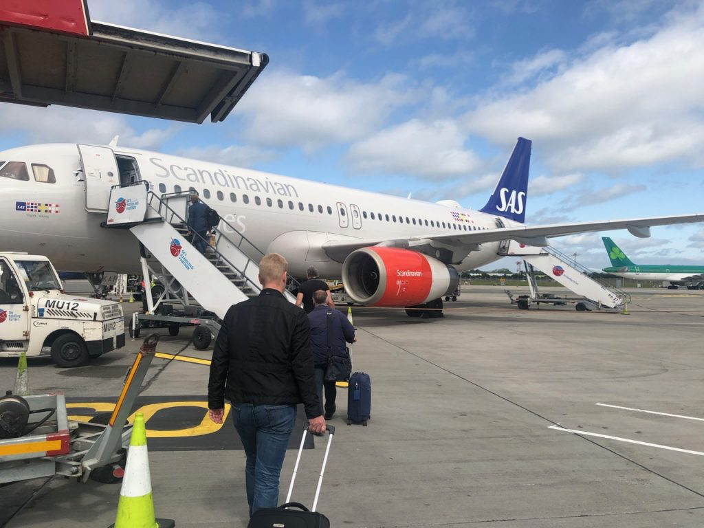 Man carrying luggage and boarding Scandinavian Airlines plane